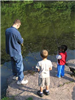 Adult showing two boys how to fish