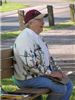 Adult sitting on bench in red cap