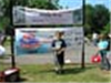 Boy in blue shirt in front of Fishing Derby sign