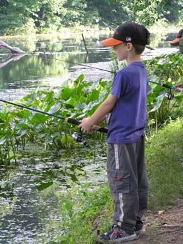 Young boy holding fishing pole at waters edge (PDF)