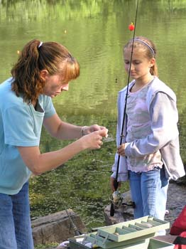 Adult helps child prepare hook for fishing pole (PDF)