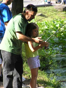 Adult teaches child how to reel in a fish (PDF)