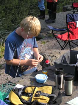 Boy prepares to bait fishing hook (PDF)