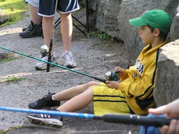 Boy sitting against rock fishing (PDF)